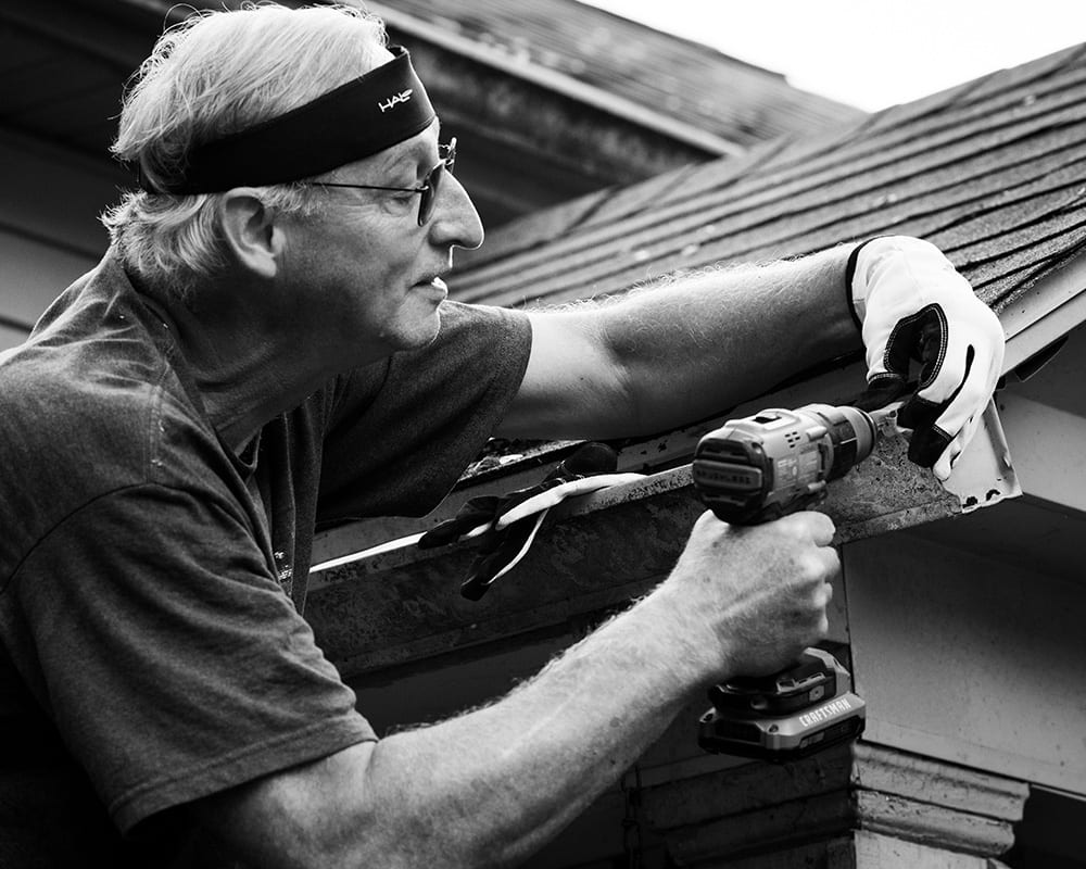 A man holding a drill works on a roof