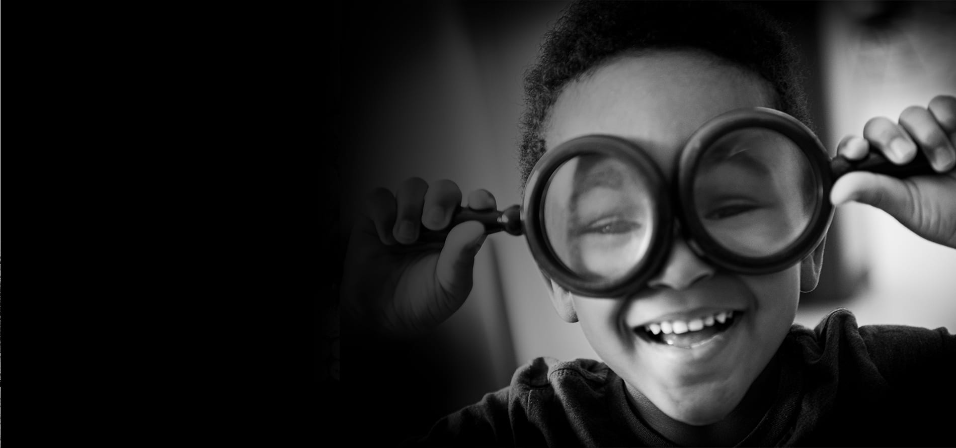 A little boy plays around with magnify glasses