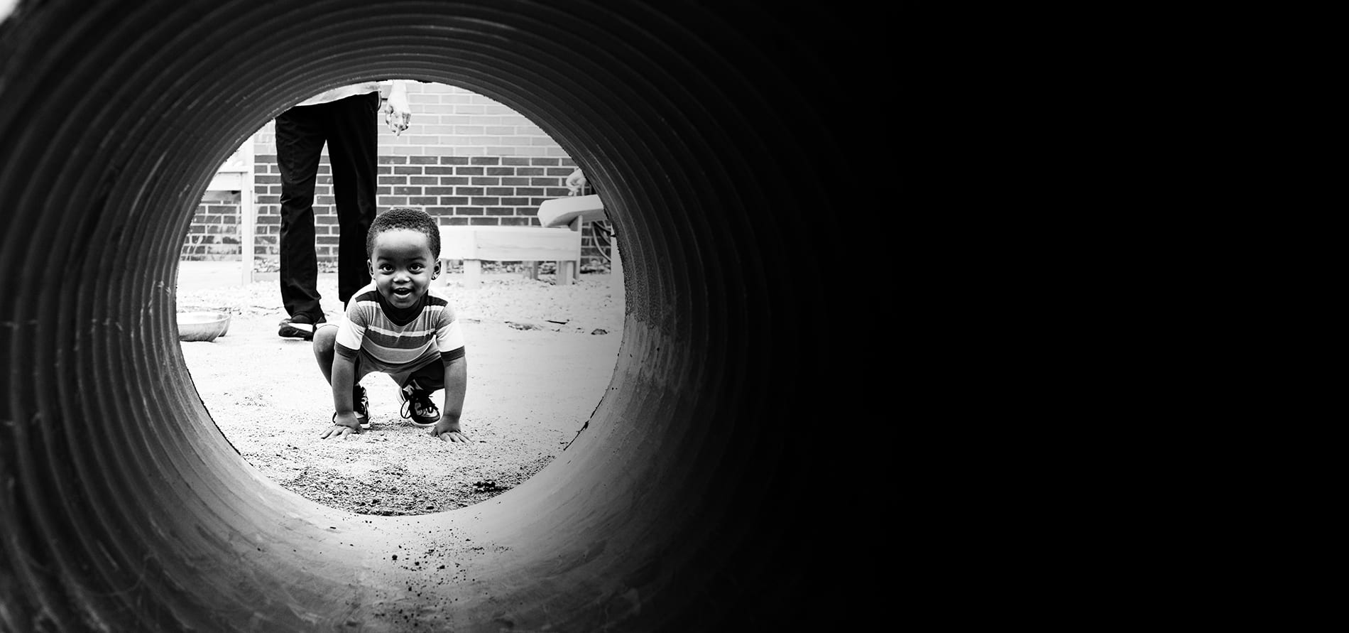 A child peeks through a tunnel