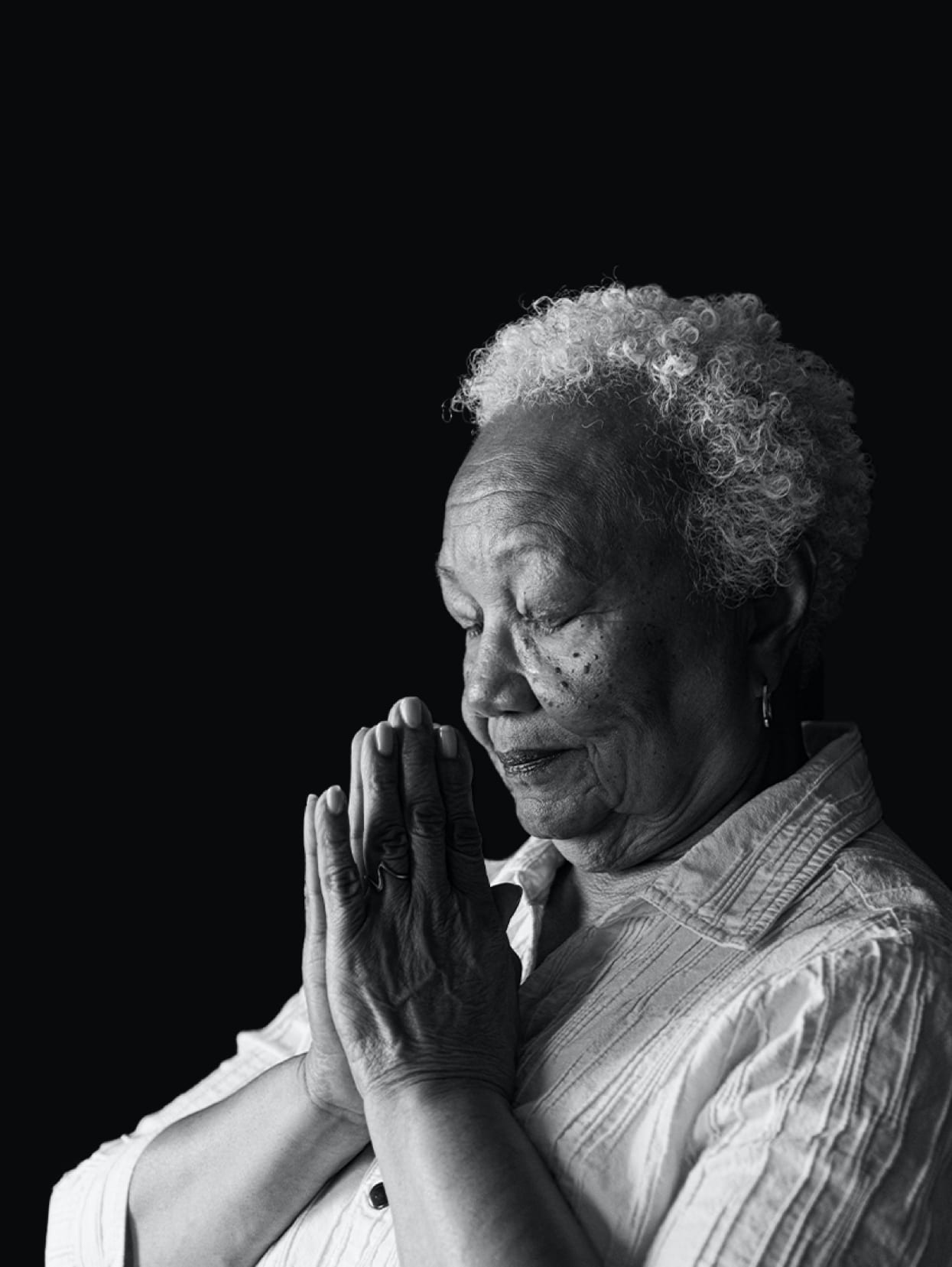 An elderly woman prays